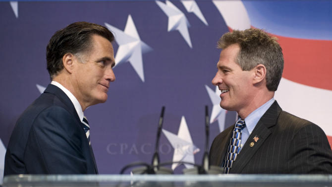 FILE - In this Feb. 18, 2010, file photo former Massachusetts Gov. Mitt Romney, left, is announced by Sen. Scott Brown, R, Mass., as he arrives on stage to speak at the Conservative Political Action Conference in Washington. The two Massachusetts Republicans have a history of supporting each other throughout their political careers, but facing tough elections neither is the presidential candidate nor the U.S. senator is playing up that history now, perhaps with good reason. (AP Photo/Cliff Owen, File)