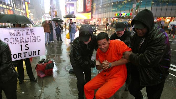 Demonstrators hold a mock waterboarding torture of a prisioner on January 11, 2008