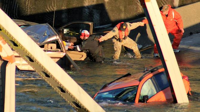 In this photo provided by Francisco Rodriguez, rescue workers form a human chain as they begin to remove a woman who reaches out from a smashed pickup truck that fell into the Skagit River after the collapse of the Interstate 5 bridgeThursday, May 23, 2013, in Mount Vernon, Wash. (AP Photo/Francisco Rodriguez)