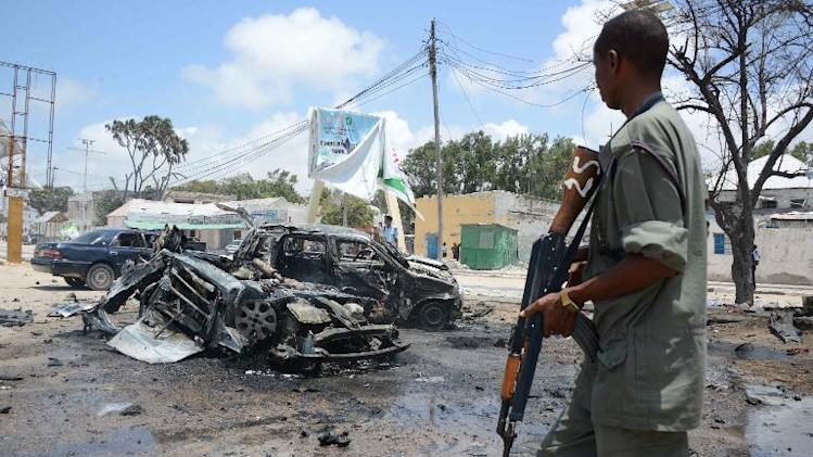 File picture shows an armed man stands guard at the scene of two explosions in Mogadishu on September 7, 2013