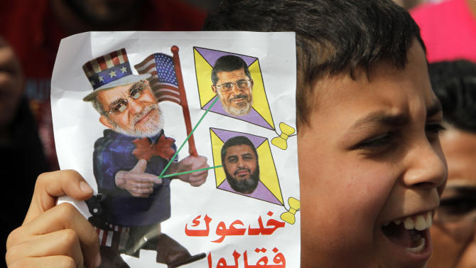 """An Egyptian boy holds a cartoon criticizing Muslim Brotherhood Supreme Leader Mohammed Badie, left, Egyptian President Mohammed Morsi, top right, and Muslim Brotherhood deputy leader Khairat el-Shater during anti-Muslim brotherhood protest, in Cairo, Egypt, Friday, March 15, 2013. Hundreds of supporters of the military gathered Friday to reject the Muslim Brotherhood and President Mohammed Morsi's rule calling for the military to return to power. Arabic reads, """" they lie to you and said our Brotherhood Leader is a king."""" (AP Photo/Amr Nabil)"""