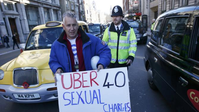 A London cab driver holds a placard during a protest by London cab drivers against Uber in central London