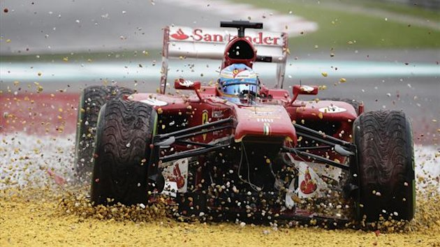 Ferrari's Fernando Alonso drives on the gravel after losing his front wing during the Malaysian Grand Prix at Sepang (Reuters)