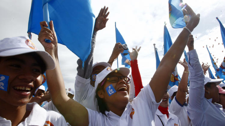 Supporters of Prime Minister Hun Sen's Cambodian People's Party hold the party's flags as they shout during the final campaign for the July 28 general election, in Phnom Penh, Cambodia, Friday, July 26, 2013. (AP Photo/Heng Sinith)