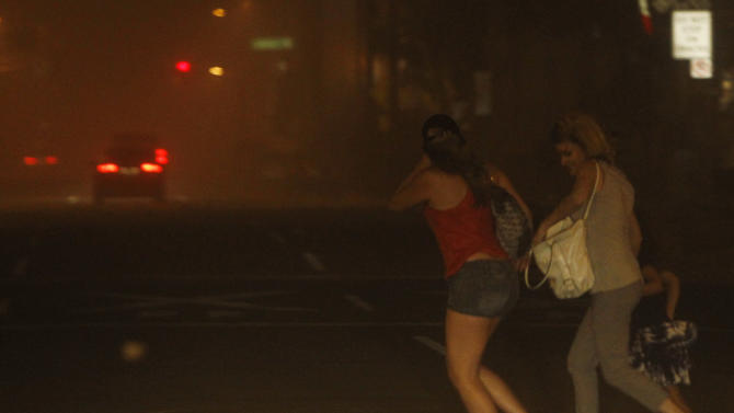 Pedestrians run to cross the street as they try to get away from a dust storm in downtown Phoenix, Tuesday, July 5, 2011.   A massive dust storm has swept into the Phoenix area and drastically reduced visibility across much of the valley.   (AP Photo/Ross D. Franklin)