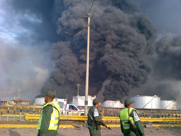 Large plumes of smoke rise from the Amuay refinery as national guards soldiers watch near Punto Fijo, Venezuela, Saturday, Aug. 25, 2012. A huge explosion rocked Venezuela's biggest oil refinery,