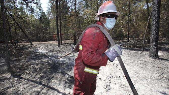 Joe Hill, a student from Texas A&M, helps steady a water hose while a fire team he is volunteering with douses hot spots on a wildfire student near Bastrop, Texas, Friday, Sept. 9, 2011. (AP Photo/LM Otero)