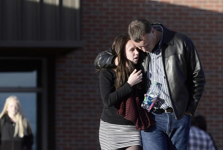 Britz, a freshman at Arapahoe High School, is comforted by her father, following a shooting incident at Arapahoe High School in Centennial, Colorado