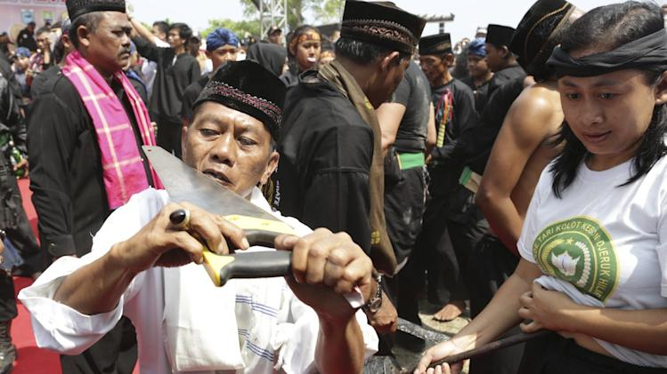 Debus players perform with a saw during Banten Beach Festival in Anyer , Banten province,Indonesia, Saturday, Aug. 23, 2014. The Debus is an ancient ceremony of the Sundanese people proving the power of faith. (AP Photo/Achmad Ibrahim)