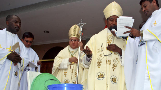 The Holy See's envoy to Tanzania Archbishop Francisco Montecillo Padilla, center-left, leads a prayer during the inauguration of the St. Joseph Mfanyakazi Roman Catholic Church, moments before it was struck by a blast in Arusha, Tanzania Sunday, May 5, 2013. A Tanzanian police official says a woman died and over 40 people were seriously injured when a bomb exploded in the Roman Catholic Church in northern Tanzania, with eyewitnesses reporting that the bomb was thrown from a motorcycle. (AP Photo)