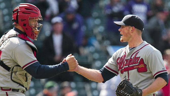 Atlanta Braves catcher Evan Gattis, left, and relief pitcher Craig Kimbrel (46) shake hands after their 4-3 win over the Colorado Rockies in the first baseball game of a doubleheader, Tuesday, April 23, 2013, in Denver. (AP Photo/Barry Gutierrez)