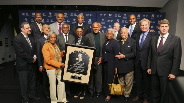 Attendees take a group photo at a news conference honoring Nelson Mandela's plaque dedication at the Yankee Stadium in New York