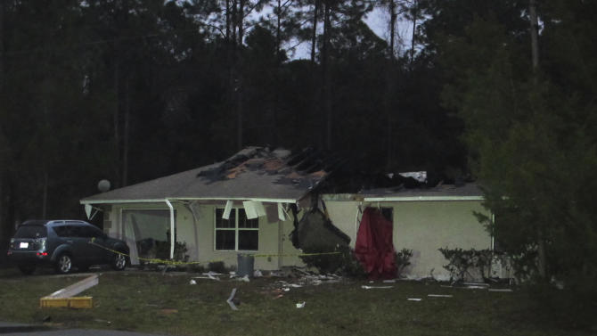 Crime scene tape surrounds the house in Palm Coast, Fla. that a small plane crashed into on Friday, Jan. 4, 2013. Authorities say at least three people are dead after the plane crashed while trying to land at Flagler County Airport. The house's occupant escaped through a window with no serious injuries. (AP Photo/Mike Schneider)