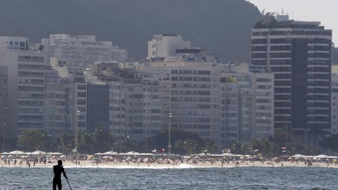 A man paddles on a stand up board on Copacabana beach in Rio de Janeiro