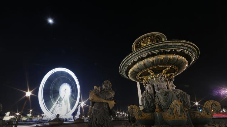 A giant Ferris wheel lights up the night sky for the Christmas holiday season on the Place de la Concorde square in Paris