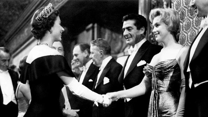 """In this late October 1956 photo provided by Running Press, Marilyn Monroe, right, wearing a burnished gold lamé gown meets the Queen in London. The photograph is included in a new 2012 book, """"Marilyn in Fashion,"""" published by Running Press. (AP Photo/Courtesy Running Press)"""