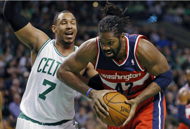 Washington Wizards' Nene Hilario (42) drives past Boston Celtics' Jared Sullinger (7) in the first quarter of an NBA basketball game in Boston, Saturday, Dec. 21, 2013