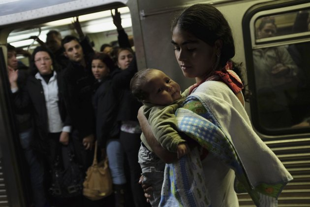 A woman holds her daughter as she waits for a train at a subway station in downtown Sao Paulo