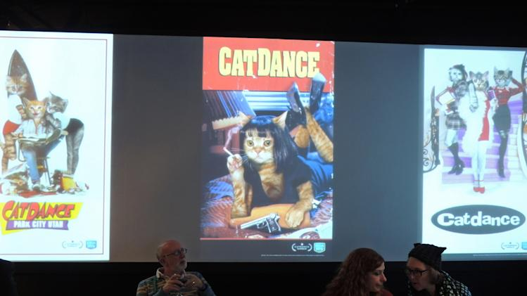 "In this Saturday, Jan. 19, 2013 photo, attendees of ""Catdance"" sit among cat-inspired spoofs of movie posters at the Sundance Film Festival in Park City, Utah. (AP Photo/Nekesa Mumbi Moody)"
