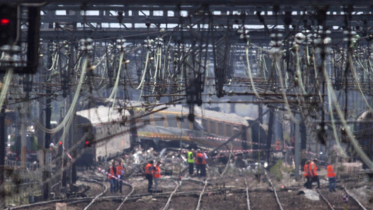 Railway's employees are seen on the scene where a train derailed at a station in Bretigny sur Orge, south of Paris, Saturday, July 13, 2013. A packed passenger train skidded off its rails after leaving Paris on Friday, leaving seven people believed dead and dozens injured as train cars slammed into each other and overturned, authorities said. France's transport minister says human error did not cause the train derailment. (AP Photo/Thibault Camus)