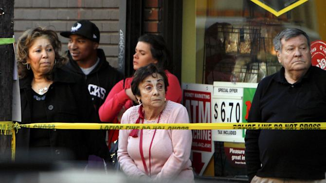 Neighbors look on as firefighters battle a blaze that burned a fabric shop, upstairs apartments and a neighboring boutique in Philadelphia, Saturday, April 6, 2013. The fire caused a partial roof collapse that killed a firefighter and injured a colleague who was trying to rescue him, officials said. (AP Photo/ Joseph Kaczmarek)