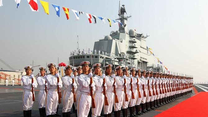 "FILE - In this Sept. 25, 2012 file photo provided by China's Xinhua News Agency, sailors stand at attention on the deck of China's aircraft carrier ""Liaoning"" in Dalian, northeast China's Liaoning Province, as China formally entered its first aircraft carrier into service. As President Barack Obama tours Southeast Asia to push his year-old pivot to the Pacific policy, the big question on everybody's mind is how much of a role Washington, with its mighty military and immense diplomatic clout, can play in keeping the Pacific peaceful. (AP Photo/Xinhua, Zha Chunming, File) NO SALES"