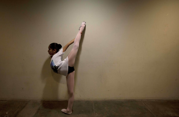 In this Sept. 3, 2012 photo, a young ballet dancer warms-up before performing in a competition between ballet schools at the National Museum in Lima, Peru. Nearly 100 girls and boys from Colombia, Venezuela, Chile, France and Peru are submitting themselves to a week-long competition hoping to win medals from Peru's national ballet school _ and perhaps a grant to study in Miami. (AP Photo/Martin Mejia)