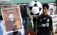 The Palestinian boy plays with a football in front of banners in solidarity with Palestinian prisoner Mahmud Al-Sarsak in Rafah town. French football icon Eric Cantona on Tuesday joined in calls for the release of Palestinian footballer Mahmud Sarsak, who is on hunger strike in an Israeli prison