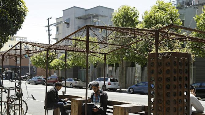 People sits at tables in a parklet outside a Mission District cafe Tuesday, June 2, 2015, in San Francisco. Finding a place to live has become so expensive and emotional that city supervisors are considering a 45-day moratorium on luxury housing in the Mission District, which has long been one of the most diverse neighborhoods in the city. (AP Photo/Eric Risberg)