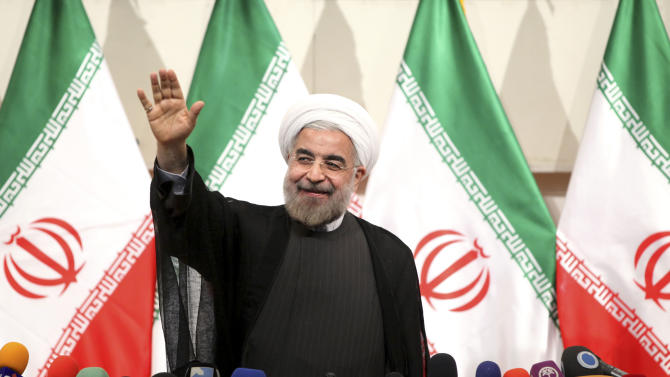 """Iranian President-elect Hasan Rowhani waves to media at the start of a press conference in Tehran, Iran, Monday, June 17, 2013. Iran's newly elected president pledged on Monday to follow a """"path of moderation"""" and promised greater openness over the country's nuclear program, but sided with the hard-line Islamic establishment that refuses to consider halting uranium enrichment. (AP Photo/Ebrahim Noroozi)"""