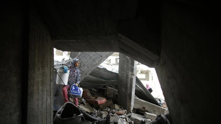 A Palestinian girl carries her belongings from her family's destroyed house in the Shejaia neighbourhood, which witnesses said was heavily hit by Israeli shelling and air strikes during an Israeli offensive, in Gaza City