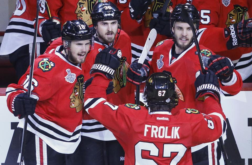 The Chicago Blackhawks celebrate a late third period goal against the Boston Bruins during Game 5 of the NHL hockey Stanley Cup Finals, Saturday, June 22, 2013, in Chicago. The Blackhawks won 3-1. (AP Photo/Charles Rex Arbogast)