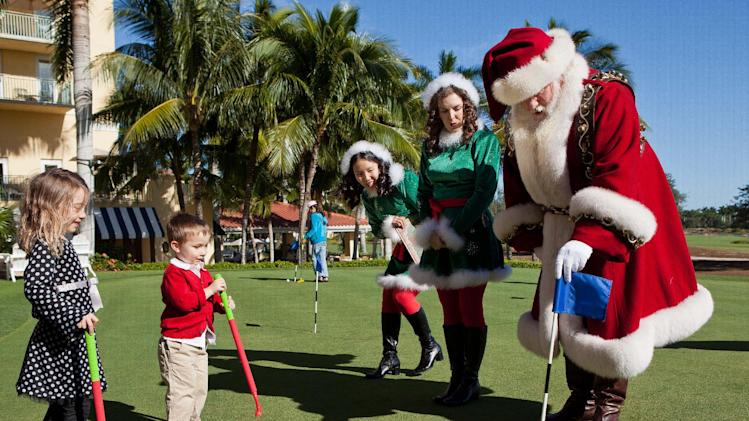 Carina Ballard, 3, left and her brother, Blake, 3, play golf with Santa Claus and his elves during the Macy's National Santa Tour at the The Ritz Carlton Golf Resort in Naples, Fla., Friday, Dec. 21, 2012. Santa made the stop at the resort to play golf with 10 Make-A-Wish children and their families as part of the Macy's national tour. (Erik Kellar/AP Images for Macy's)