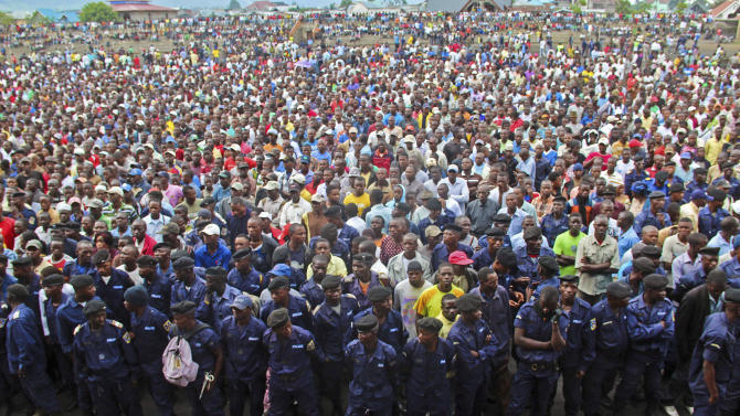 Congo government policemen, foreground,  and civilians gather during a M23 rally in Goma, Congo, Wednesday, Nov. 21, 2012. A rebel group believed to be backed by Rwanda seized the strategic, provincial capital of Goma in eastern Congo on Tuesday, home to more than 1 million people as well as an international airport in a development that threatens to spark a new, regional war, officials and witnesses said.(AP Photo/Melanie Gouby)