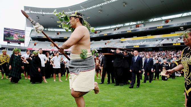 A Maori warrior leads the official party carrying the casket of former All Black player Jonah Lomu during a memorial service at Eden Park in Auckland, New Zealand