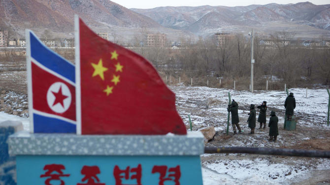 "In this Saturday, Dec. 8, 2012 photo, Chinese paramilitary policemen build a fence near a concrete marker depicting the North Korean and Chinese national flags with the words ""China North Korea Border"" at a crossing in the Chinese border town of Tumen in eastern China's Jilin province. (AP Photo/Ng Han Guan)"