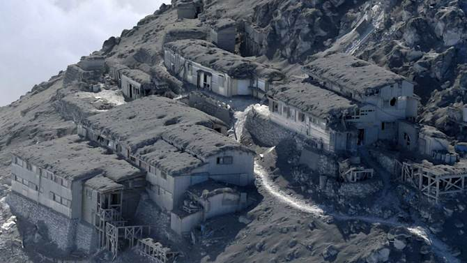 An aerial view shows mountain lodges with heavily damaged roof top in the erupted Mount Ontake, central Japan, Monday, Sept. 29, 2014. Japanese soldiers managed to bring down eight more bodies by helicopter from the ash-blanketed peak of a still-erupting volcano on Monday, before toxic gases and ash forced them to suspend the recovery effort in the early afternoon.(AP Photo/Kyodo News) JAPAN OUT, MANDATORY CREDIT