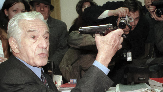 A picture taken on Dec. 21, 1999 shows film director Sergiu Nicolaescu pointing a gun at his head in the former Communist Party building in Bucharest, Romania, while describing to journalists the way Romania's last communist regime Defense Minister Gen. Milea killed himself on Dec 22 1989. Sergiu Nicolaescu, a prolific Romanian director known for his historical epics who also served as a Senator, has died on Thursday, Jan.3, 2013. He was 82. The Elias Hospital said Nicolaescu died Thursday from heart and lung complications following surgery for digestive problems.(AP Photo/Eugeniu Salabasev)