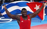 Mijain Lopez Nunan of Cuba celebrates after defeating Estonia&#39;s Heiki Nabi during their 120kg Greco Roman Wrestling Final match of the London 2012 Olympic Games at the Excel Centre in London on August 6, 2012. AFP PHOTO/ MANAN VATSYAYANA
