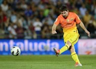 Barcelona's forward Lionel Messi shoots a penalty to score during a Spanish league football match against Getafe at the Alfonso Perez stadium in Getafe near Madrid. Barcelona made it four wins in four games with a 4-1 victory at Getafe to stay two points ahead of Malaga, who had earlier beaten Levante 3-1, at the top of La Liga