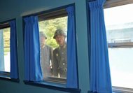 North Korean soldiers look through a window in the truce village of Panmunjom. There are no civilian mail or phone connections across the closely guarded inter-Korean border, and many do not even know whether their loved ones are still alive