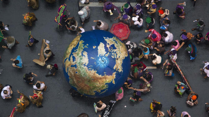 Activists push an inflatable globe during a