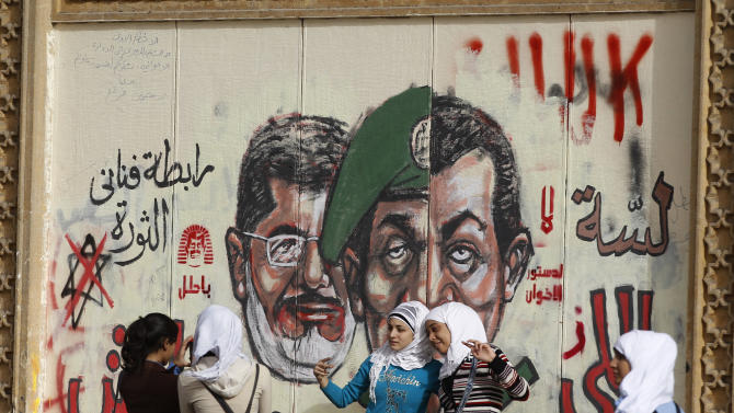 Young girls pose for a photograph by a wall painted with graffiti showing President Mohammed Morsi, left, and a split portrait of former Defense Minister, Hussain Tantawi, center, and former President Hosni Mobarak, right, in front of the Presidential Palace in Cairo, Egypt, Monday, Dec. 10, 2012. The Egyptian military on Monday assumed joint responsibility with the police for security and protecting state institutions until the results of a Dec. 15 constitutional referendum are announced. (AP Photo/Petr David Josek)