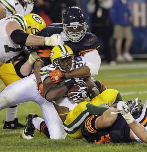 Green Bay Packers running back Brandon Jackson (32) is tackled by Chicago Bears defensive end Julius Peppers and linebacker Brian Urlacher, bottom, during the second half of an NFL football game Monday, Sept. 27, 2010, in Chicago. At left is Packers offensive tackle Chad Clifton. The Bears won 20-17. (AP Photo/Charles Rex Arbogast)
