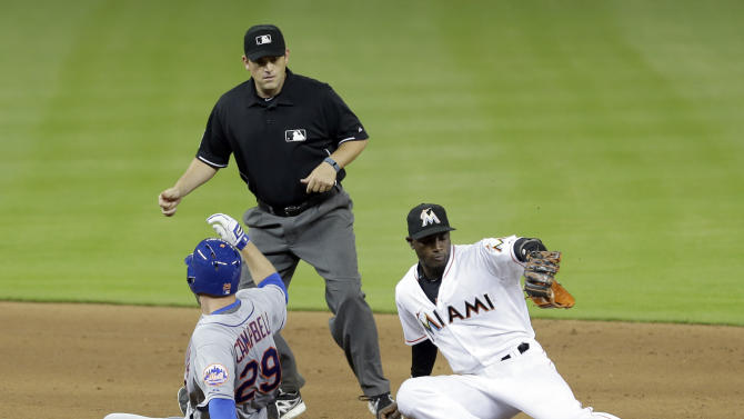 New York Mets' Eric Campbell (29) slides safely into second base on a double as Miami Marlins shortstop Adeiny Hechavarria, right, catches the late throw in front of second base umpire Brian Knight, in the ninth inning of a baseball game, Monday, April 27, 2015, in Miami. The Mets won 3-1. (AP Photo/Alan Diaz)