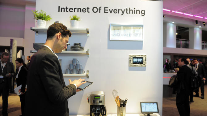 "In this Tuesday, Feb. 26, 2013, photo, a man checks his device in front of a banner ""Internet of Everything"" at the Mobile World Congress, the world's largest mobile phone trade show, in Barcelona, Spain. The first wave of the wireless revolution was getting people to talk to each other through cellphones. The second, it seems, will be getting things to talk to each other, with no human intervention: cars that talk to your insurance company's computers, bathroom scales that talk to your phone, and electric meters that talk to your air conditioners. So-called machine-to-machine technology all the buzz at this year's largest wireless trade show, and some analysts believe these types of connections will outgrow the traditional phone business in less than a decade. (AP Photo/Manu Fernandez)"