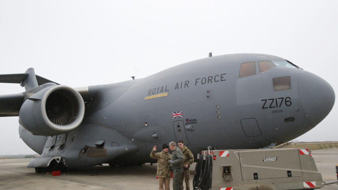 A French airman, center, talks to British military personnel prior to the take off a British C17 transport plane enroute to Mali at the French army base in Evreux, 90 kms(56 mls)north of Paris, Monday, Jan. 14, 2013. British military equipment was readied for deployment in Mali on Monday as international intervention in the country increased following advances in the north by Islamic extremists with reported links to Al-Qaida. Two C-17 transport planes have arrived at the French military airbase at Evreux, bound for Mali. Two C-17 transport planes have arrived at the French military airbase at Evreux, bound for Mali. (AP Photo/Michel Euler)