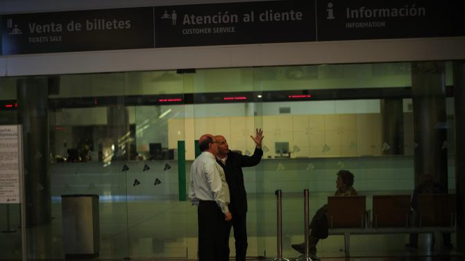 A Renfe worker (L) talks to a passenger as they look at an information board before the departure of a train, running minimum services, at Malaga Maria Zambrano train station, in Malaga