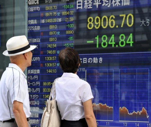 <p>An elderly couple gaze at a share prices board in the window of a securities company in Tokyo on September 26. Asian markets were mostly lower on Monday as better-than-expected US growth data failed to offset concerns over corporate earnings.</p>