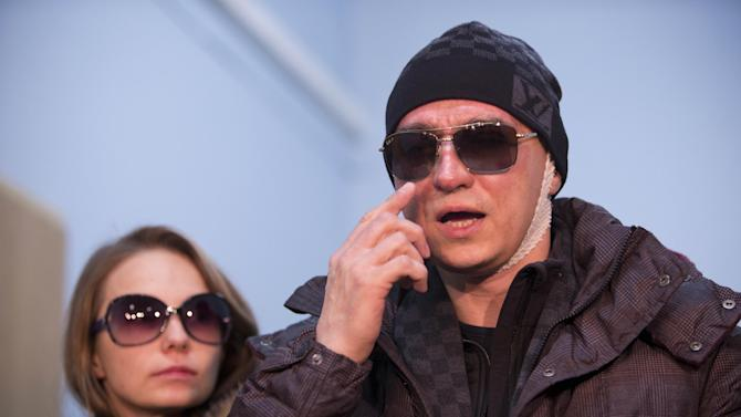 Artistic director of the Bolshoi ballet Sergei Filin, right,, and his wife Maria, speak with the media as he leaves a hospital in Moscow, Russia, Monday, Feb. 4, 2013. Filin was attacked in Moscow on Thursday night, Jan. 17, 2013, by a man who splashed acid onto his face as the 43-year-old former dancer came out of his car outside his home in central Moscow. (AP Photo/Misha Japaridze)